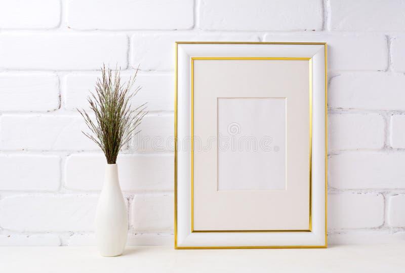 Goud verfraaid kadermodel met donker gras in vaas dichtbij baksteen w stock afbeelding