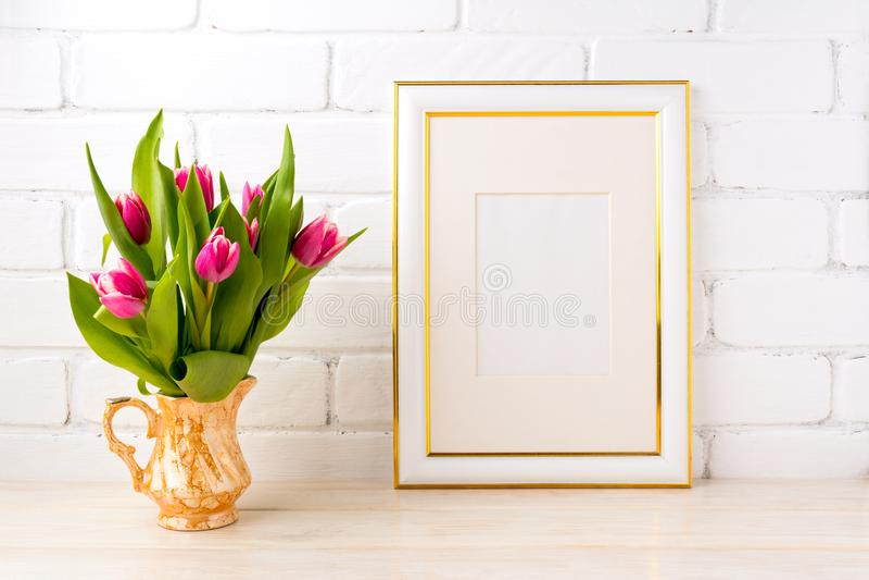 Goud verfraaid kadermodel met roze tulpen in kruik stock foto