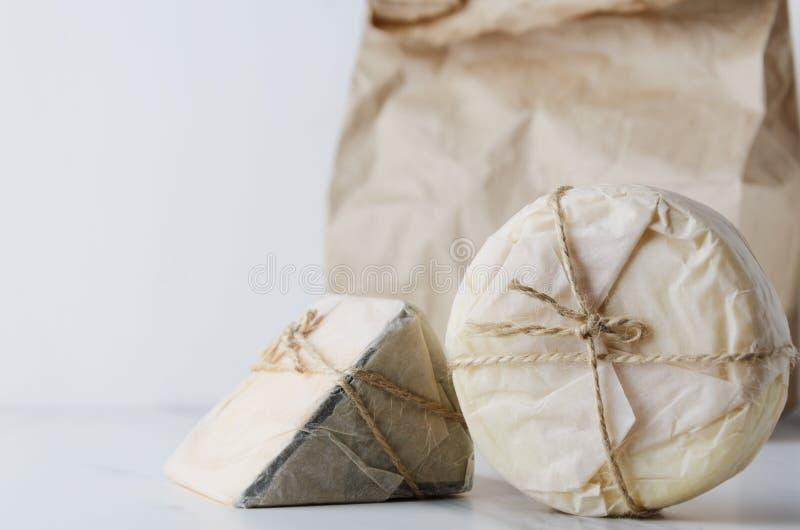 Gouda saboroso, camembert embalado no papel contra o pacote do eco na tabela branca fotografia de stock