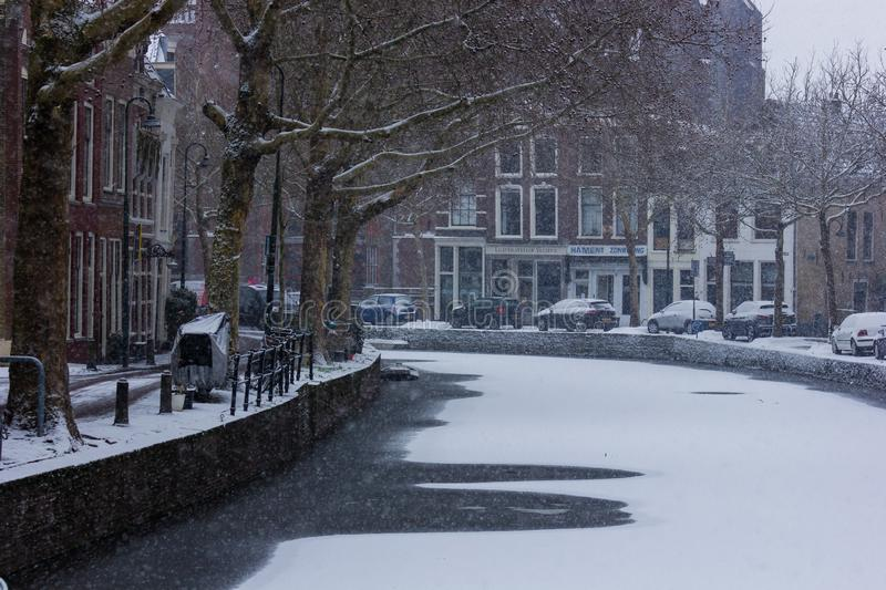 Gouda, South-Holland/The Netherlands - January 22 2019: First real snow in the Netherlands in 2019 a walk through the inner city. Of Gouda view on the water and stock photography
