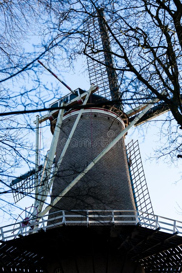 Gouda, South Holland/the Netherlands - January 20 2019: Picture of old windmill next to city park taken through tree branches stock images