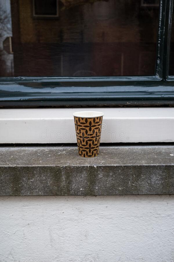 Gouda, South Holland/the Netherlands - March 1 2020: Cardboard coffee cup left behind in the window sill in the city center of. Gouda stock photo