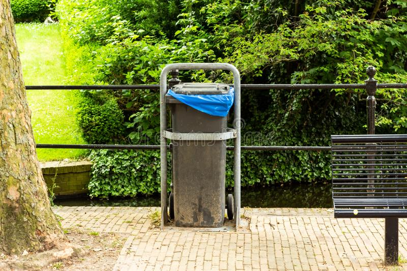 Gouda, South Holland/The Netherlands - May 19 2018: Modern day grey plastic trash container in public area of city center of Gouda. With a blue garbage back stock photography