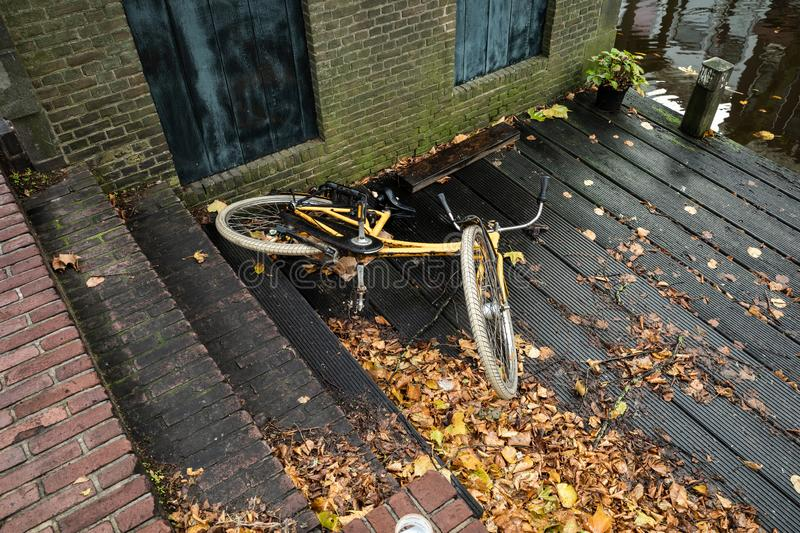 Gouda, South Holland/The Netherlands - November 3 2019: Bike fallen of small stone steps laying on the wooden deck shot with the. Ricoh GR3 stock image