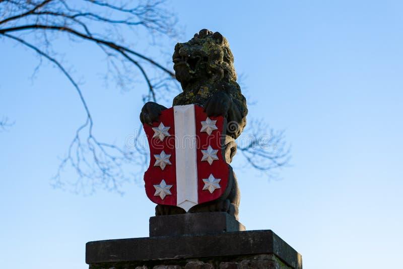Gouda, Zuid-Holland/Nederland - Januari 20 2019: portret van het leeuwstandbeeld wordt geschoten met het embleem van de Goudastad stock foto