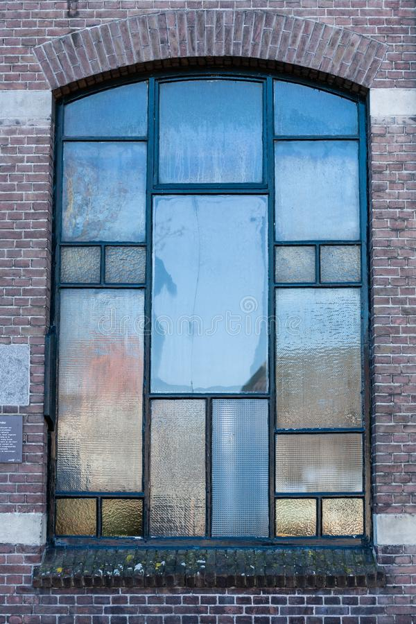 Gouda, Zuid-Holland/Nederland - Januari 20 2019: portretstijl van een oud glas paneld venster wordt geschoten in een oud gebouw d stock foto