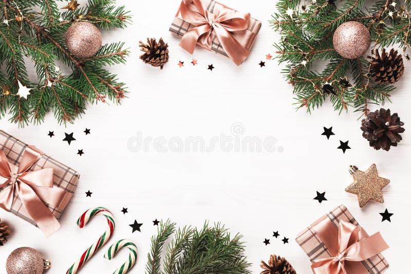 Goudbubbels, geschenken verpakt in ambachtelijk papier, dennenaaltje, confetti op wit hout Kerstvlakke laag met versieringen en c royalty-vrije stock fotografie