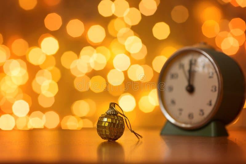 Gouden bal en klok op de achtergrond van onscherpe lichten royalty-vrije stock fotografie
