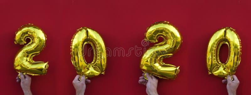 Gouden ballons in handen tegen rode achtergrond Concept Nieuwjaar 2020 stock fotografie