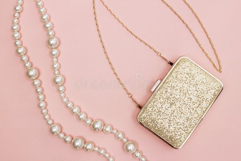 Gouden beurs en parelhalsband op roze achtergrond stock foto