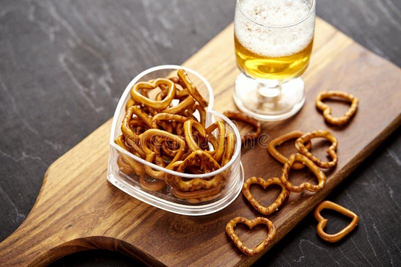 Gouden bier en heerlijke zoute pretzels op een oude zwarte houten lijst stock fotografie