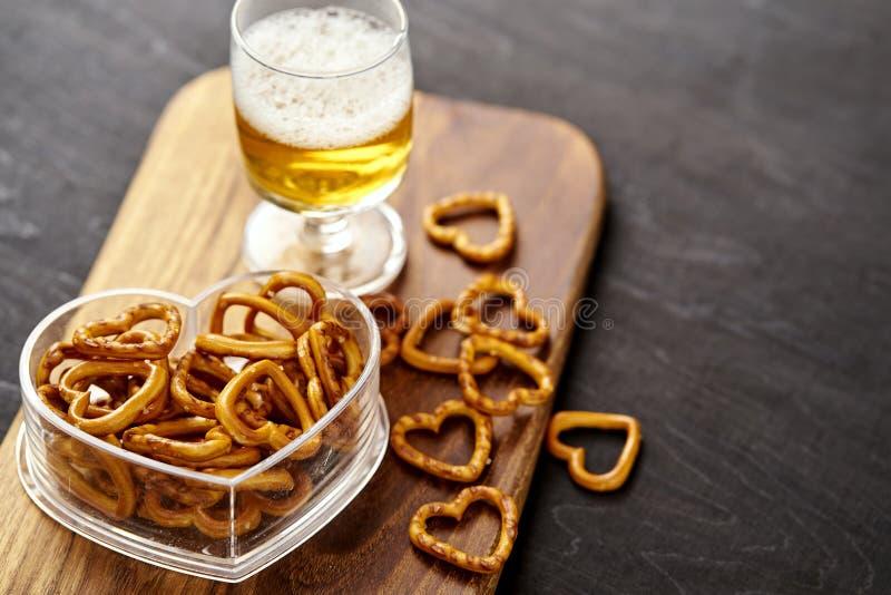 Gouden bier en heerlijke zoute pretzels op een oude zwarte houten lijst royalty-vrije stock fotografie