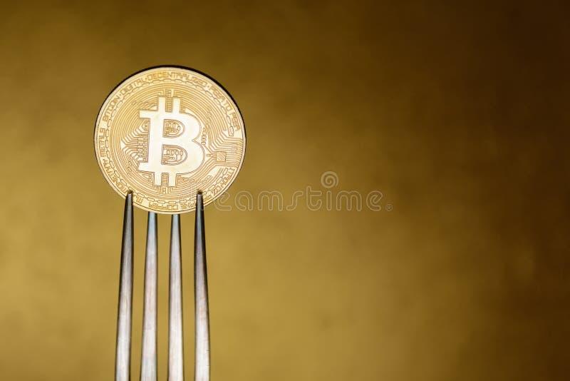 Gouden bitcoin binnen met zilveren vork stock foto