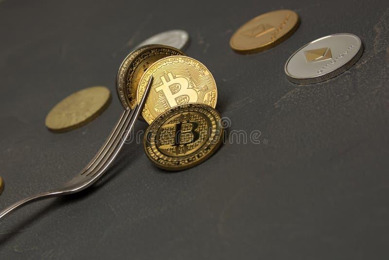 Gouden bitcoin binnen met zilveren vork met andere crypto munt stock afbeeldingen