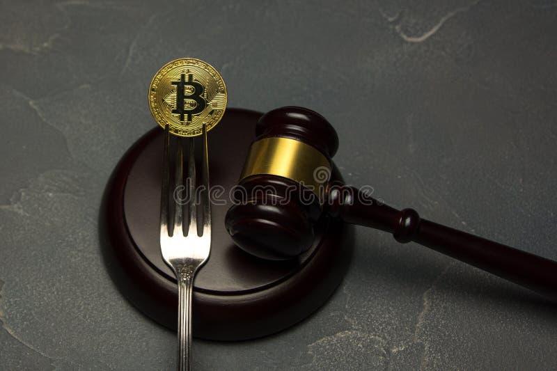 Gouden bitcoin binnen met zilveren vork met rechtershamer royalty-vrije stock afbeeldingen