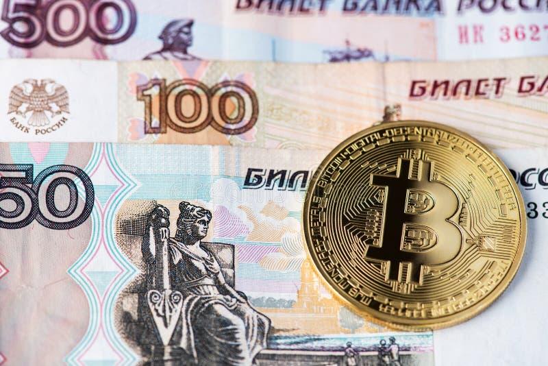 Gouden Bitcoin-cryptocurrency op Russische Roebelsbankbiljetten stock foto's