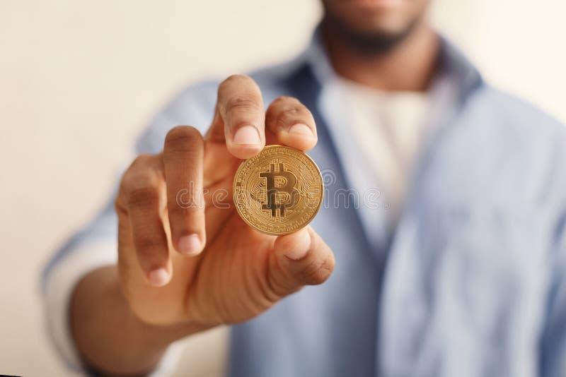 Gouden bitcoin in de Afrikaans-Amerikaanse close-up van de mensenhand stock foto