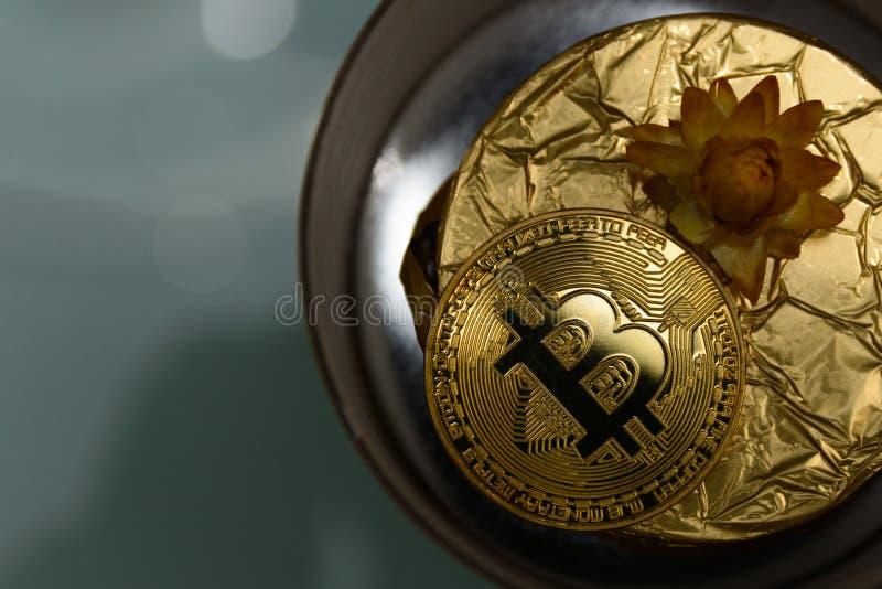 Gouden bitcoin ligt op gouden gift stock afbeelding