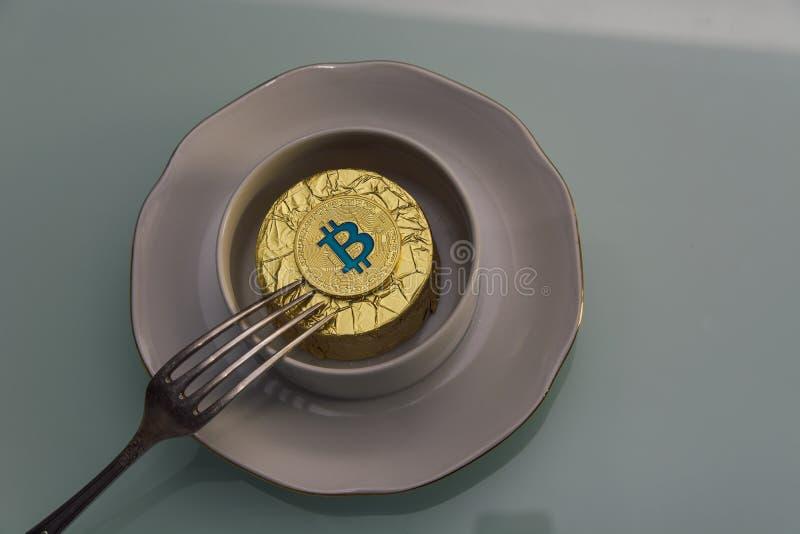 Gouden bitcoin ligt in witte kop op schotel met zilveren vork stock foto