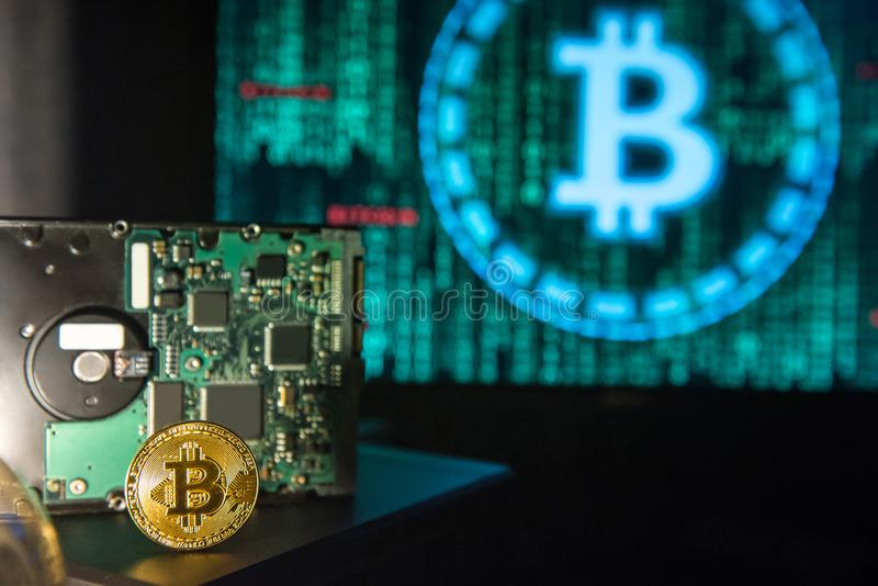 Gouden Bitcoin met harde schijf, het groene binaire scherm in backgrou stock foto's