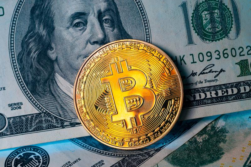 Gouden Bitcoin-muntstuk op ons de achtergrond van dollarrekeningen royalty-vrije stock afbeeldingen