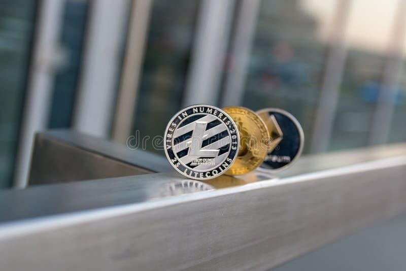 Gouden bitcoin zilveren litecoin en ethereum op metaalleuning stock afbeeldingen