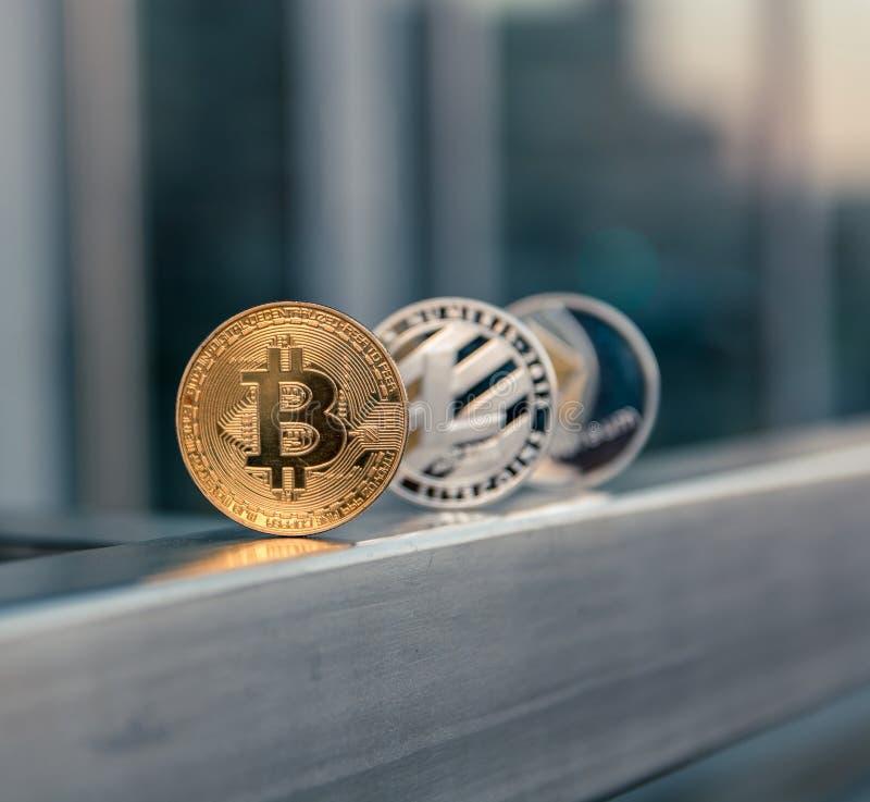 Gouden bitcoin zilveren litecoin en ethereum op metaalleuning stock foto