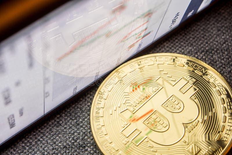 Gouden bitcoinmuntstuk met een grafiekbezinning over zijn oppervlakte stock afbeeldingen