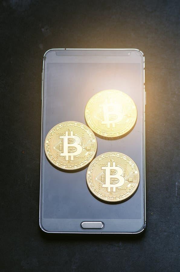 Gouden bitcoinmuntstukken op een slimme telefoon Virtuele munt Crypto munt nieuw virtueel geld Abstracte verlichtingsachtergronde royalty-vrije stock foto's