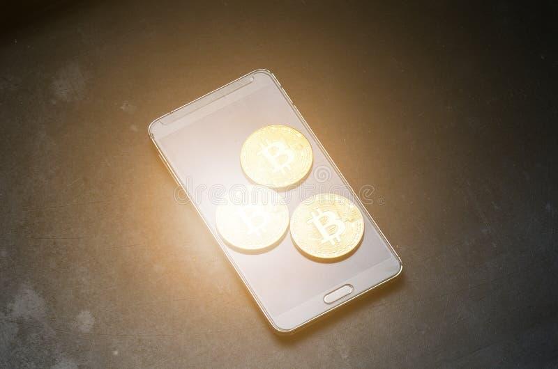 Gouden bitcoinmuntstukken op een slimme telefoon Virtuele munt Crypto munt nieuw virtueel geld Abstracte verlichtingsachtergronde stock fotografie