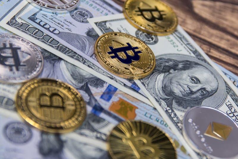 Gouden bitcoins en ethereum liggen op honderd dollarsrekeningen royalty-vrije stock afbeelding