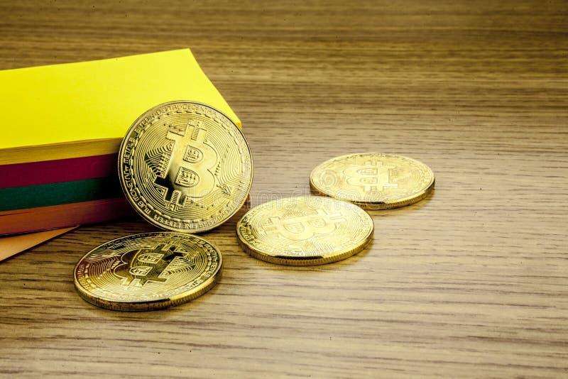 Gouden bitcoins op houten bureau, cryptocurrencyachtergrond met document nota's 3D Illustratie stock foto