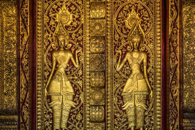Gouden Boeddhistisch deurbeeldhouwwerk stock afbeeldingen