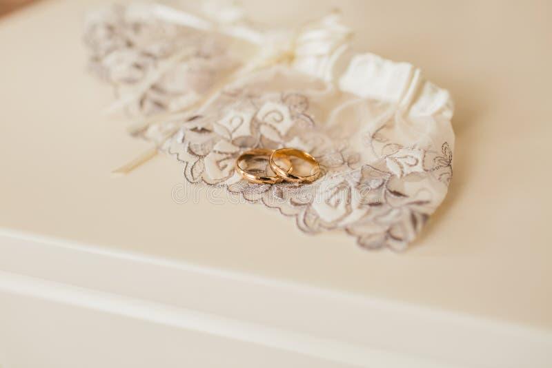 Gouden bruiloftringen die op kantkouseband leggen op een witte lijst Kousebanden en kousen kunstwerk stock foto