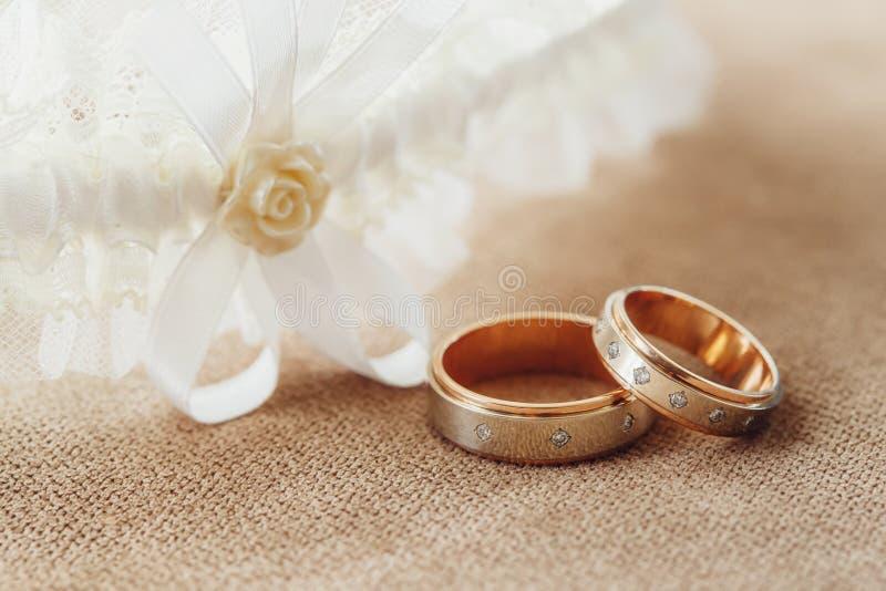 Gouden bruiloftringen en kouseband van de bruid, huwelijksconcept royalty-vrije stock foto