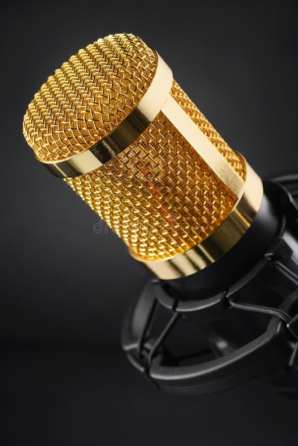 Gouden condensatormicrofoon op zwarte stock afbeelding
