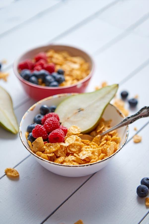 Gouden cornflakes met verse vruchten van frambozen, bosbessen en peer in ceramische kom royalty-vrije stock afbeeldingen