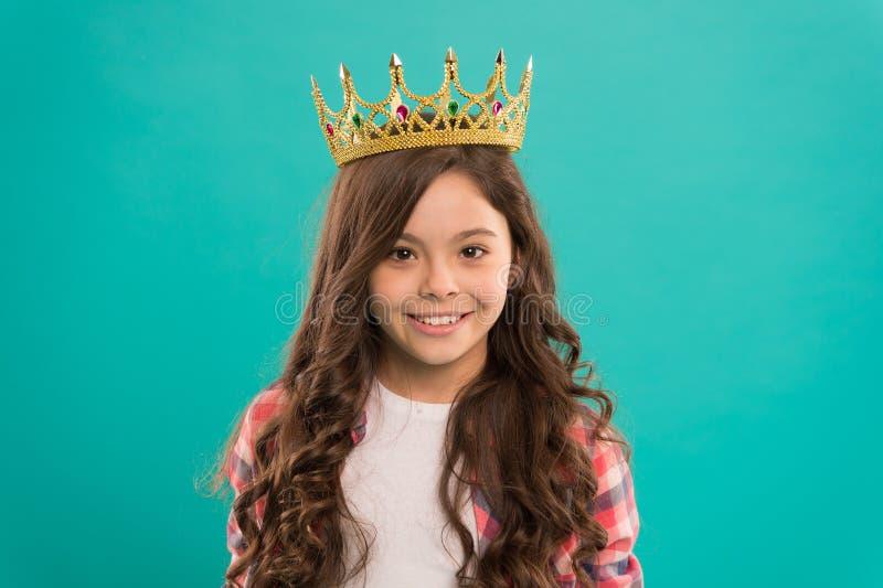 Gouden de kroonsymbool van de jong geitjeslijtage van prinses De slijtagekroon van de meisjes leuke baby terwijl tribune blauwe a royalty-vrije stock fotografie