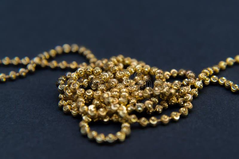 Gouden die halsband op zwarte achtergrond, macroclose-up wordt geïsoleerd showin stock afbeelding