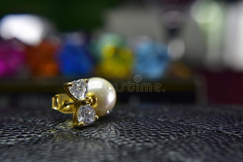 Gouden die pareloorringen met mooie diamanten worden verfraaid stock foto's