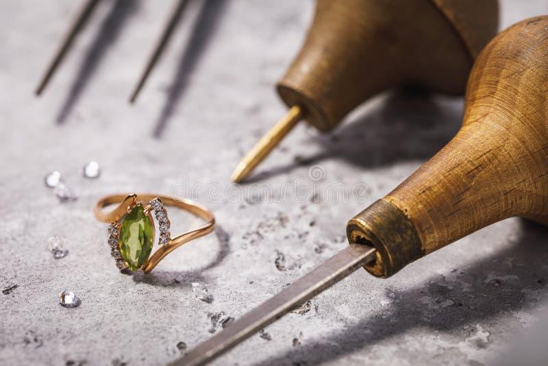 Gouden die ring met edelstenen op de lijst, door de hulpmiddelen van de juwelenreparatie wordt omringd stock foto's