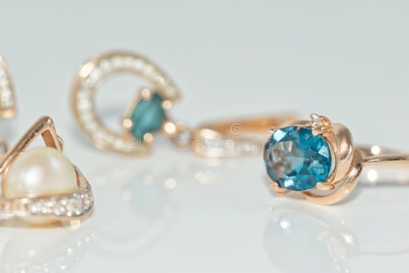 Gouden die ringen en oorringen met edelstenen worden ingelegd stock afbeeldingen