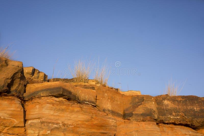 Gouden die zandsteenklippen door zonsondergang worden aangestoken stock afbeeldingen