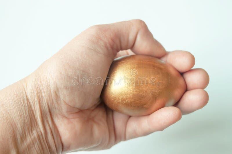 Gouden ei in de hand stock foto