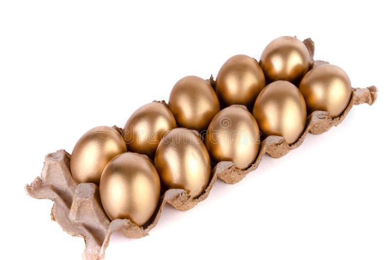 Gouden ei en jast eieren in een kartondoos op een witte achtergrond stock afbeeldingen