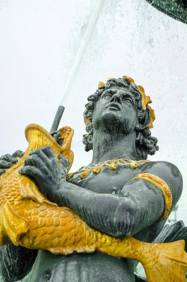 Gouden en bronsstandbeeld van een mens met een vis royalty-vrije stock foto