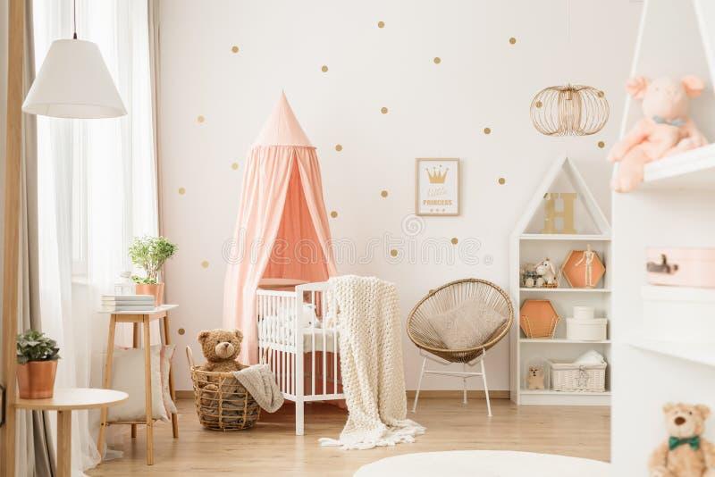 Gouden en roze baby` s slaapkamer stock foto's