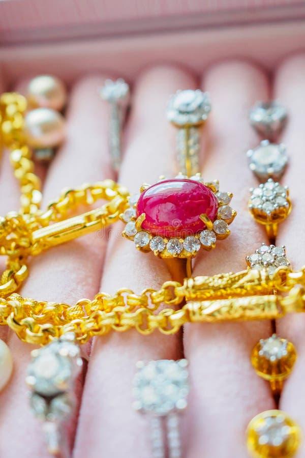 Gouden en zilveren de ringshalsbanden van de diamanthalfedelsteen en pareloorringen in juwelendoos royalty-vrije stock foto's