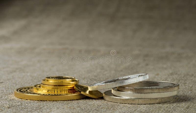 Gouden en zilveren muntstukken in dichte omhooggaand op de achtergrond van de stoffentextuur royalty-vrije stock foto