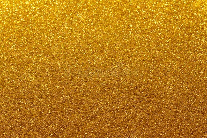 Gouden Feestelijke Kerstmisachtergrond De samenvatting fonkelde heldere achtergrond met bokeh defocused gouden lichten stock foto's